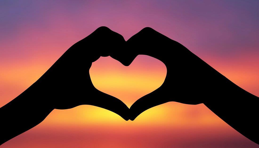 Dos manos juntas hacen la forma de un corazón.