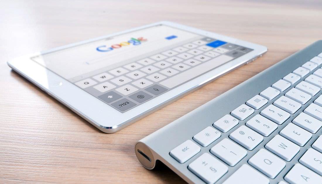 Se aprecia una tablet acompañada de un teclado, donde se muestra la pantalla de inicio del buscador de Google.