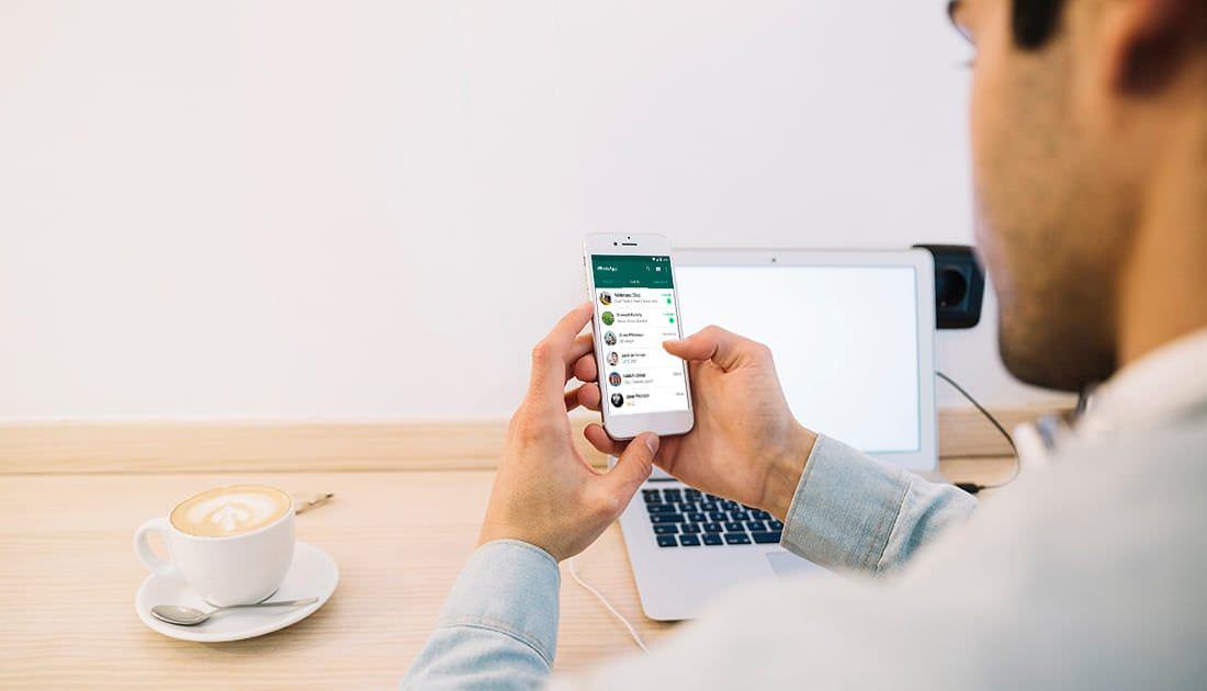 Trabajador usando WhatsApp para comunicarse con sus clientes
