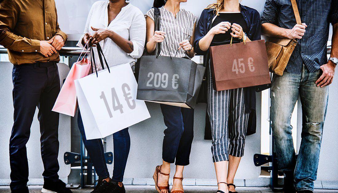 Un grupo de personas cargan con sus compras recién hechas.